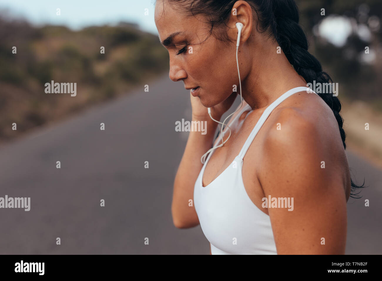 Side view of a female athlete wearing earphones listening to music while on training session. Sportswoman listening to music outdoors in morning. - Stock Image