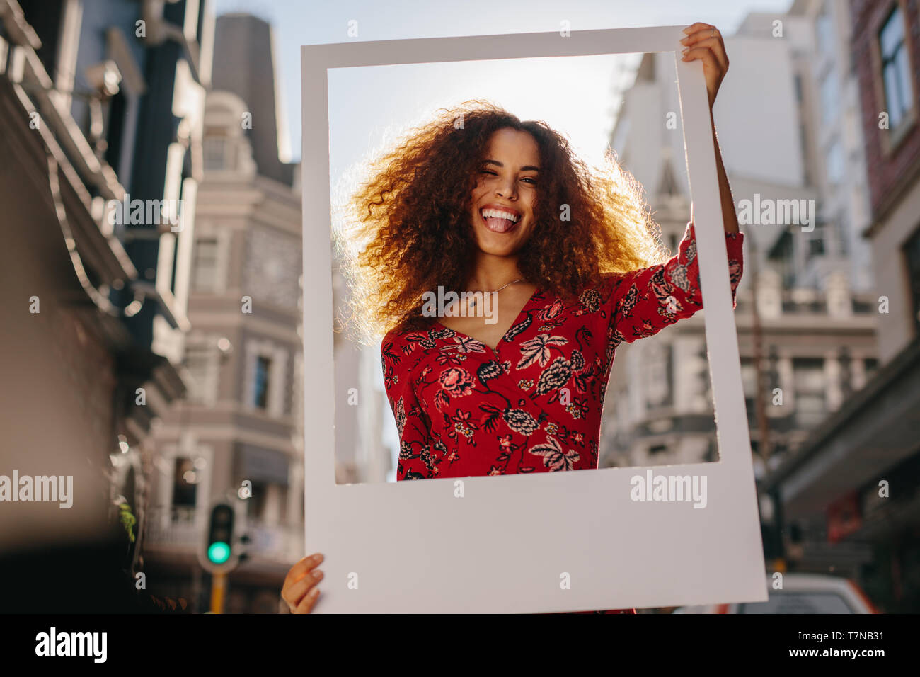 Mixed race woman with curly hair wearing sundress sticking out tongue and looking through blank photo frame . Beautiful female with big picture frame  - Stock Image