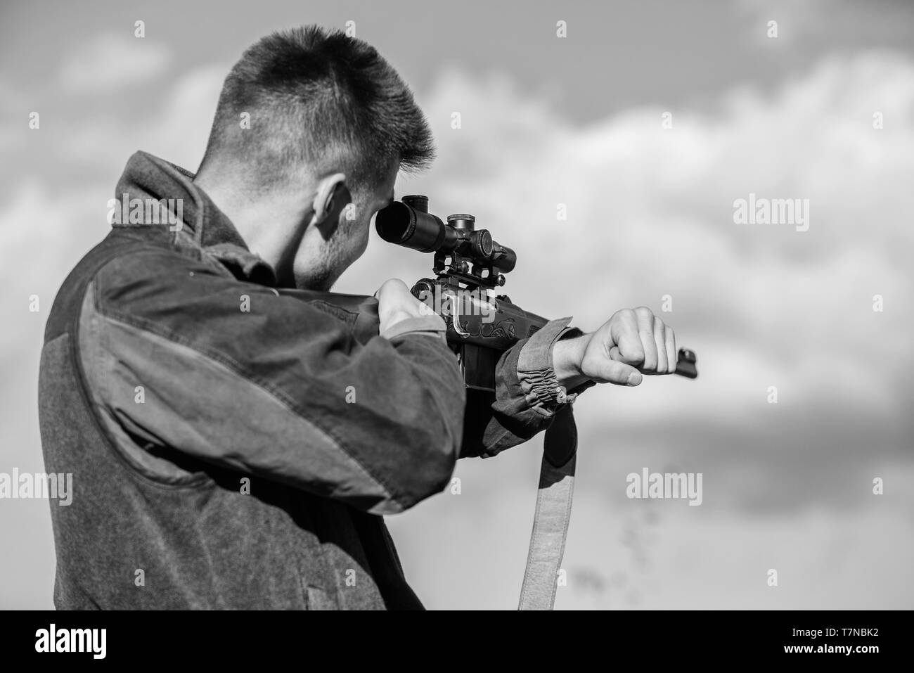 Hunting optics equipment for professionals. Brutal masculine hobby. Man aiming target nature background. Aiming skills. Hunter hold rifle aiming. On my target. Bearded hunter spend leisure hunting. - Stock Image
