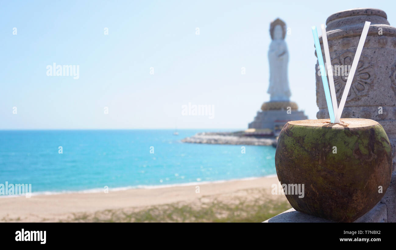 Guanyin of Nanshan, the white statue of the bodhisattva Guanyi near the Nanshan Temple of Sanya, China. In the foreground a coconut cocktail, the sea Stock Photo