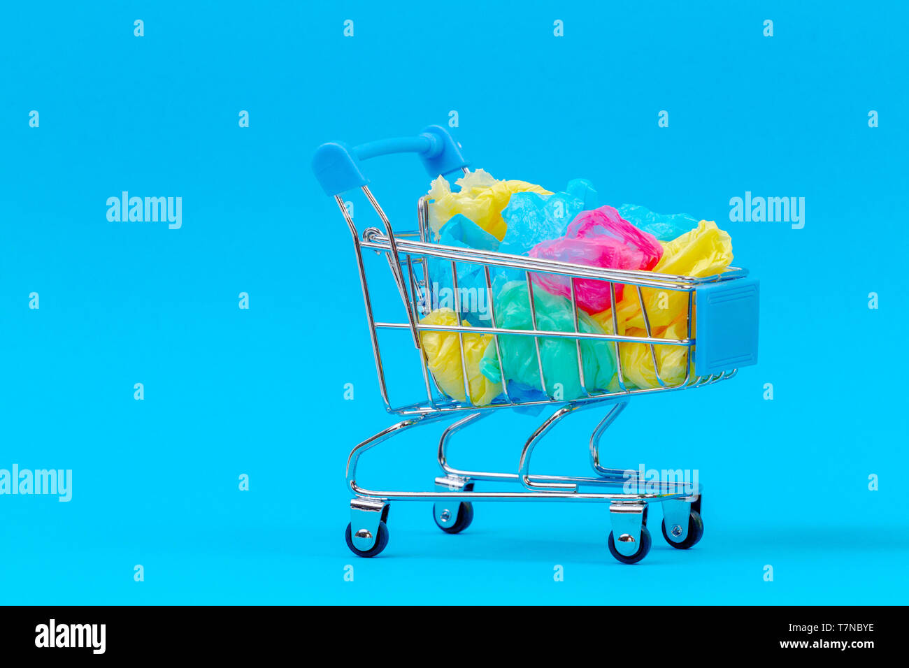 Mini shopping trolley full of colorful single use plastic bags on blue background - Stock Image