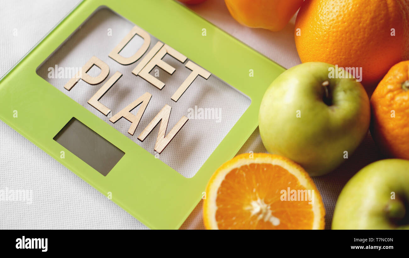 Concept diet. Healthy food, kitchen weight scale. Vegetables and fruits lettering Diet plan Stock Photo