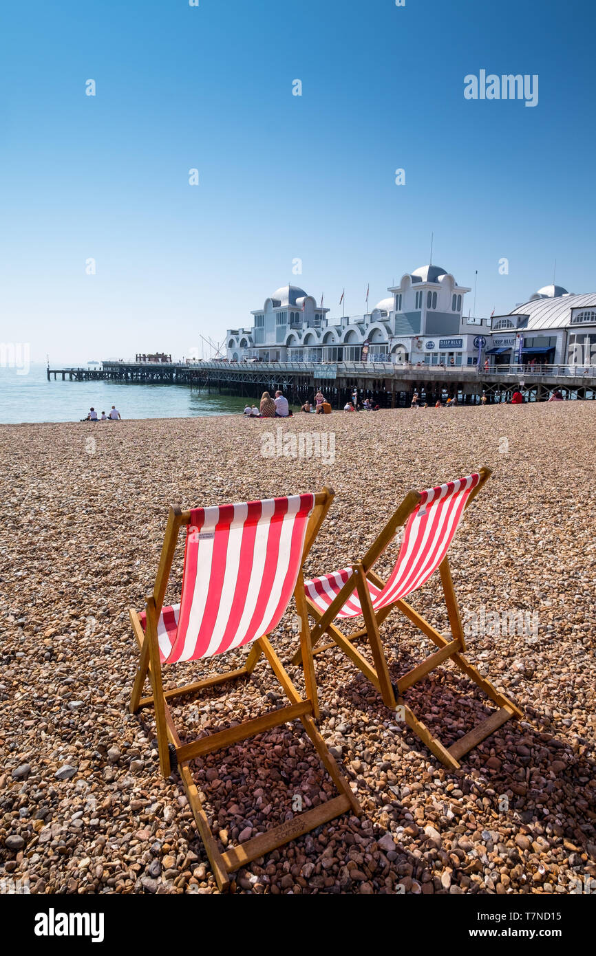 Deckchairs on Southsea beach with South Parade Pier in the background, Southsea, Portsmouth, Hampshire, UK - Stock Image