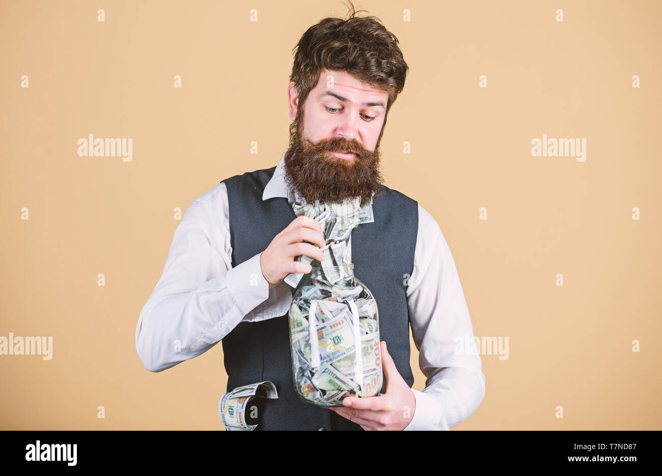 Personal accountant. Businessman with his dollar savings. Richness and wellbeing. Security and money savings. Banking concept. Man bearded guy hold jar full of cash savings. Safe place to keep money. - Stock Image