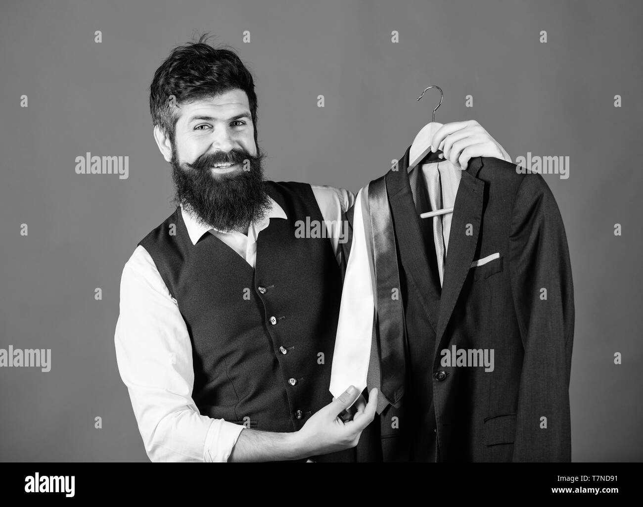 Shop assistant or personal stylist service. Matching necktie outfit. Man bearded hipster hold neckties and formal suit. Perfect necktie. Shopping concept. Stylist advice. Difficulty choosing necktie. - Stock Image