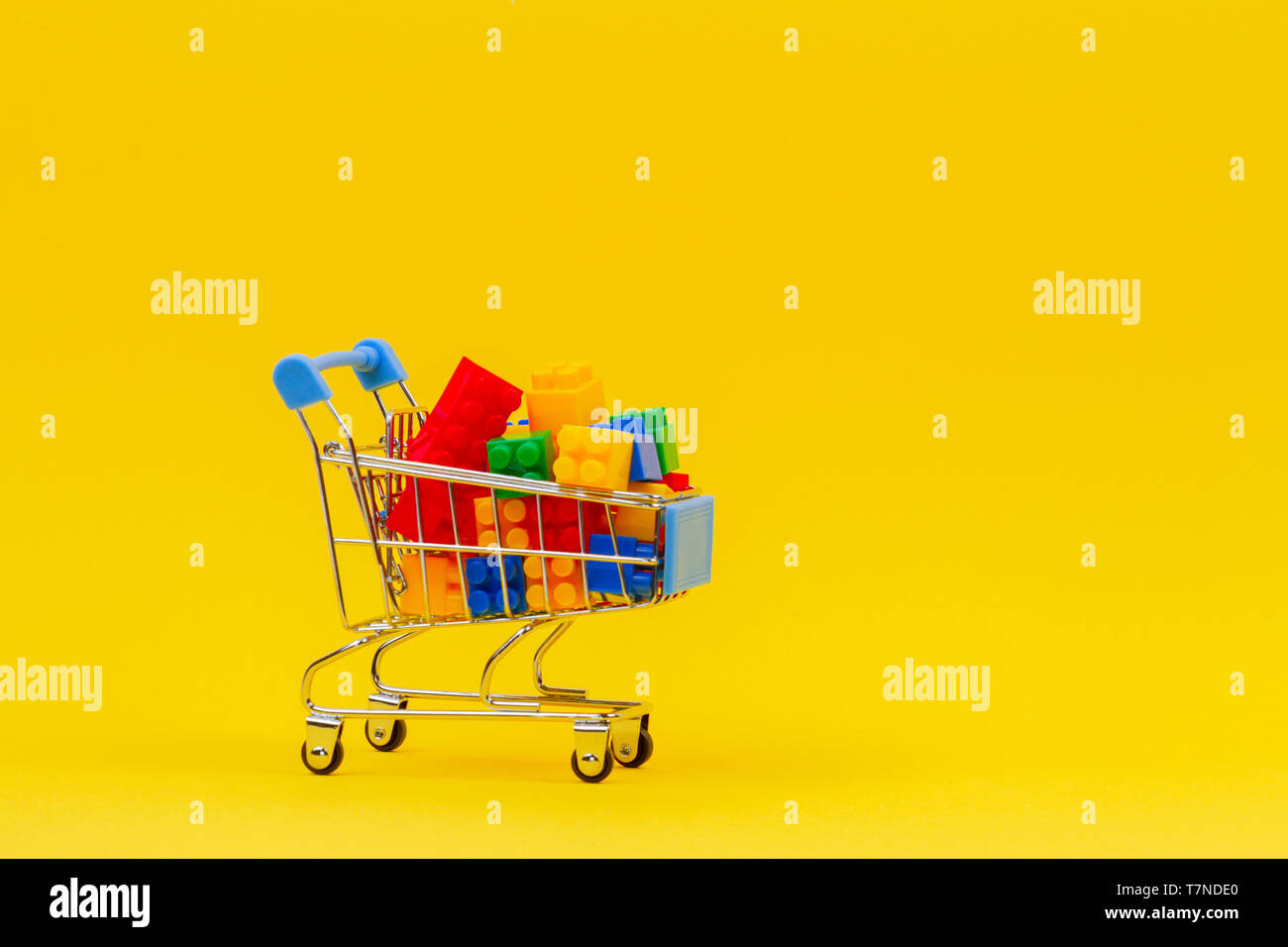 Shopping trolley cart full of colorful bricks on yellow background - Stock Image
