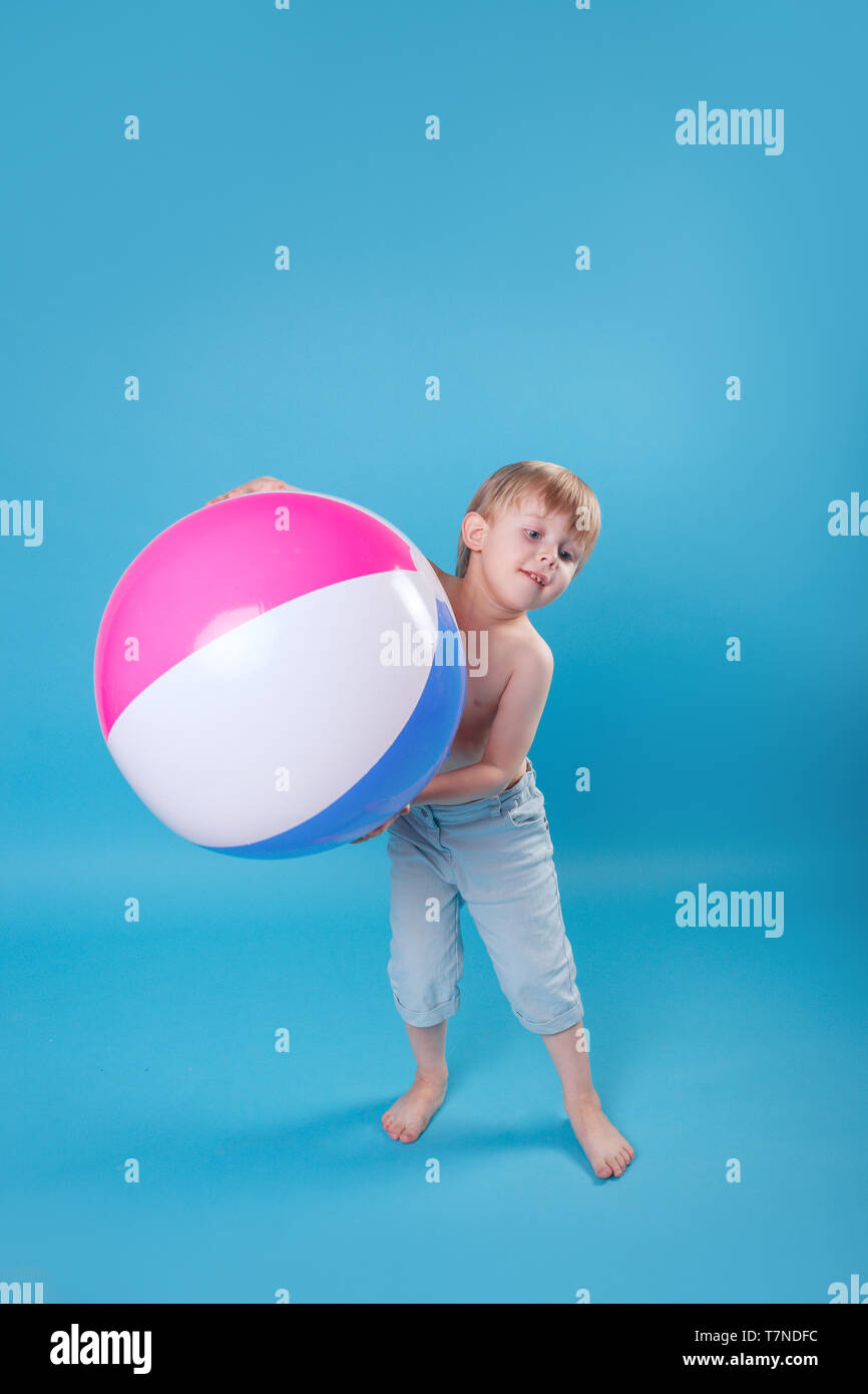 8f127e9238 Cute Llttle boy in swimming shorts holding a beach ball on blue background  - Stock Image
