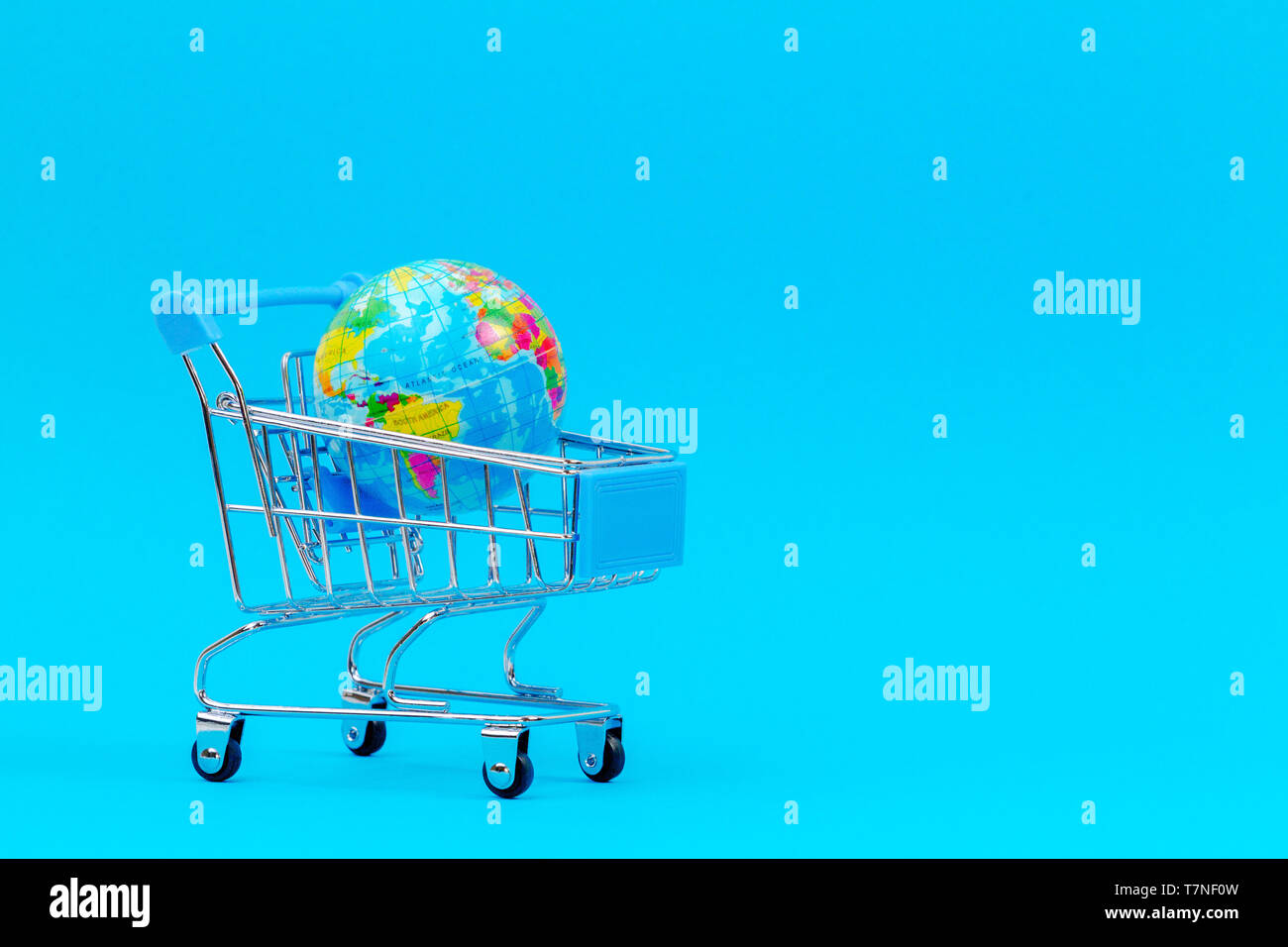 Mini shopping trolley cart with with globe on blue background - Stock Image