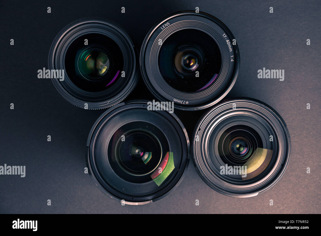 Set of various DSLR lenses with colorful reflections - shot from above - Stock Image