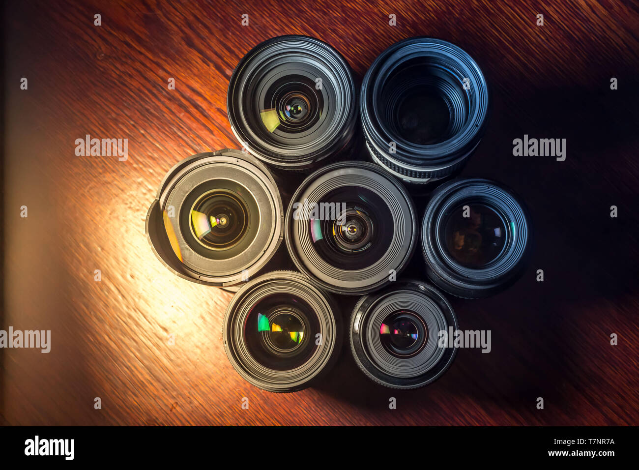 Set of various DSLR lenses with colorful reflections - shot from above on wooden background - Stock Image