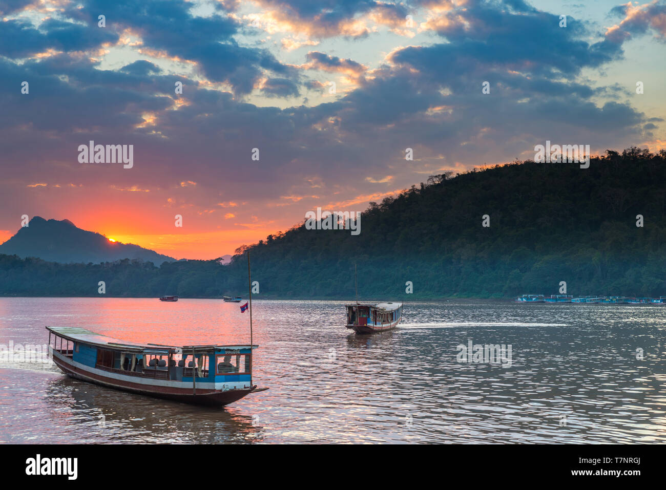 Boats on Mekong River at Luang Prabang Laos, sunset dramatic sky, famous travel destination backpacker in South East Asia Stock Photo