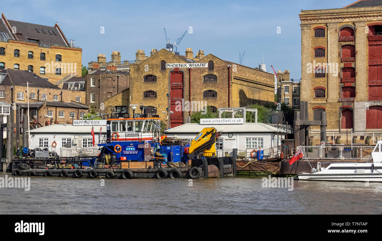 WAPPING, LONDON: The riverfront seen from the river Thames with pier and Wharfs - Stock Image