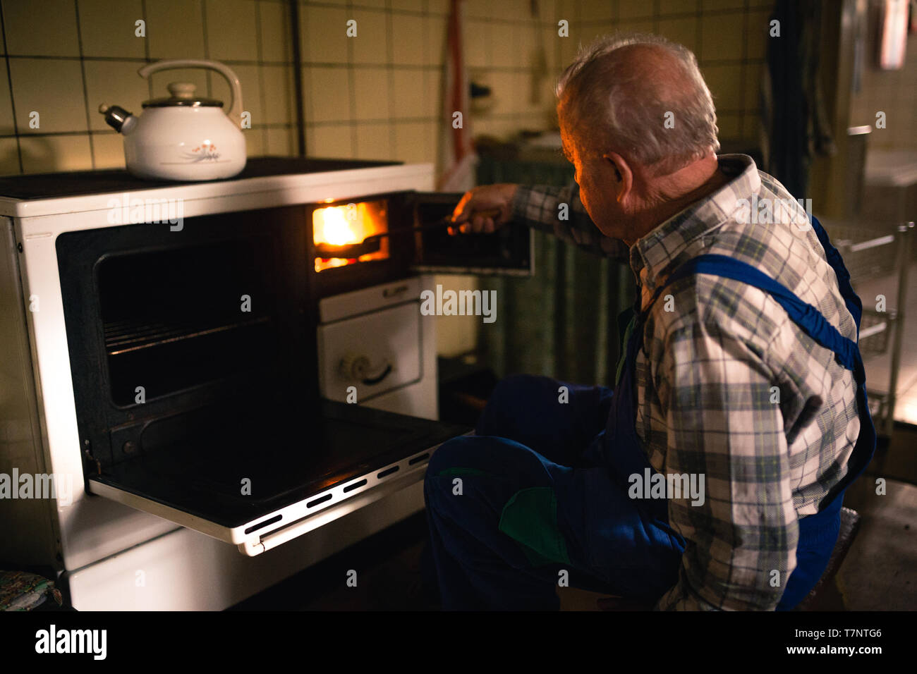 Old man putting coal in to the stove in the cottage - Stock Image