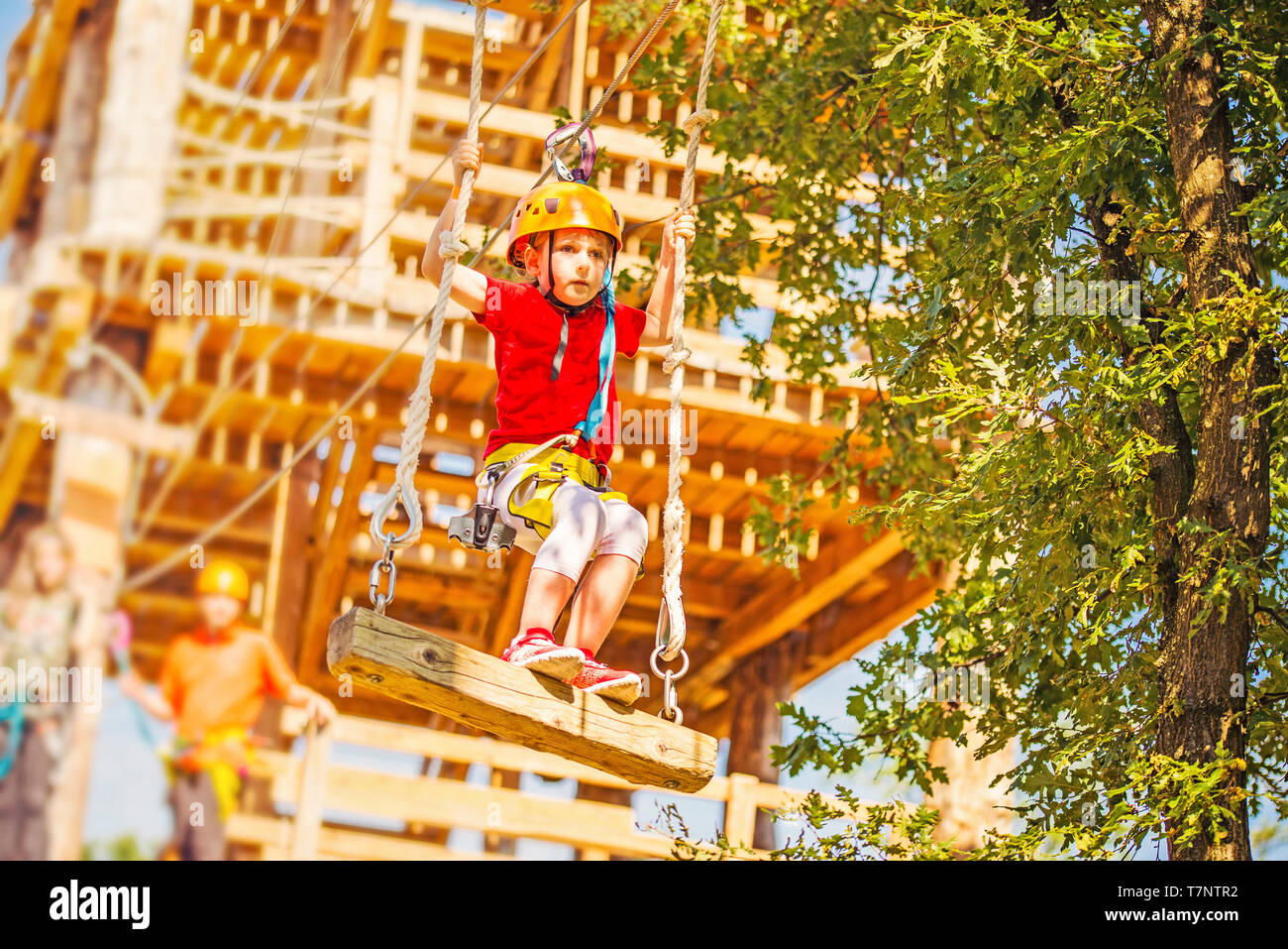 Little caucasian girl using a zip line in a rope playground structure. - Stock Image