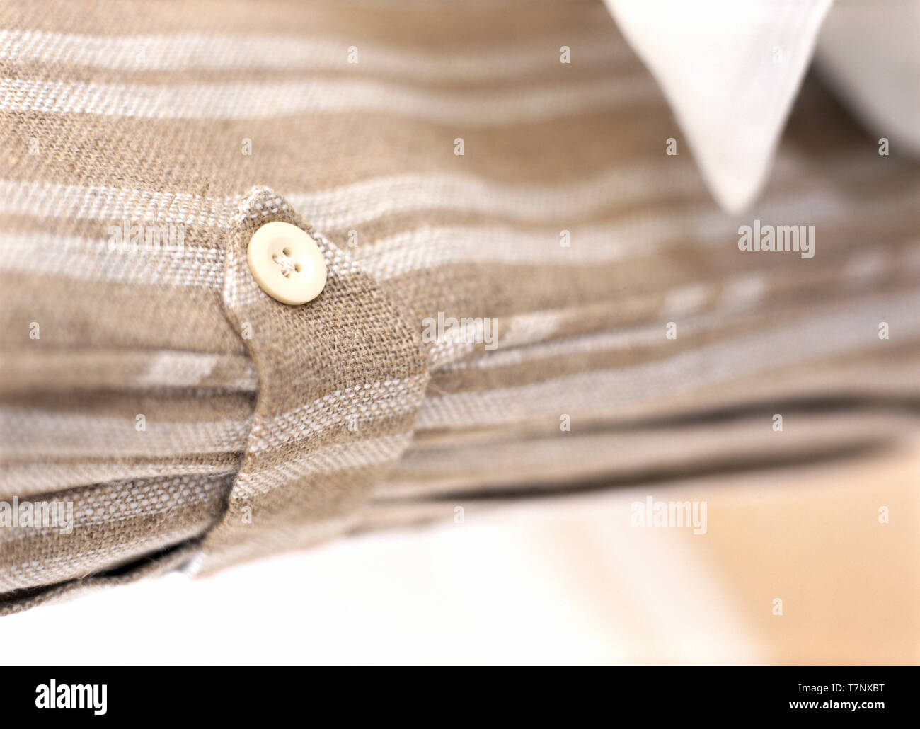 Close-up of striped curtain with buttoned tie back - Stock Image
