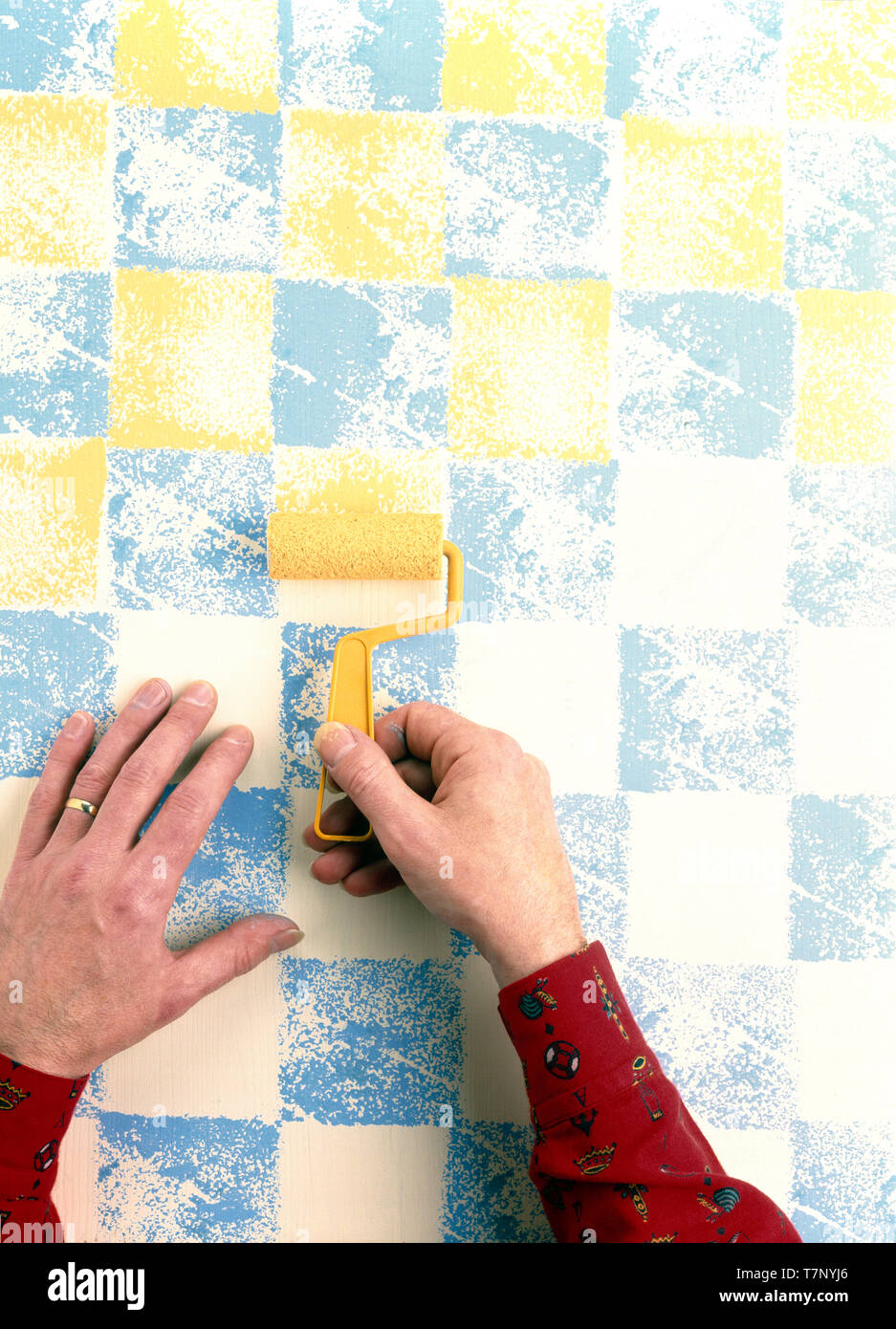 Hand using roller to paint chequerboard pattern on wall - Stock Image