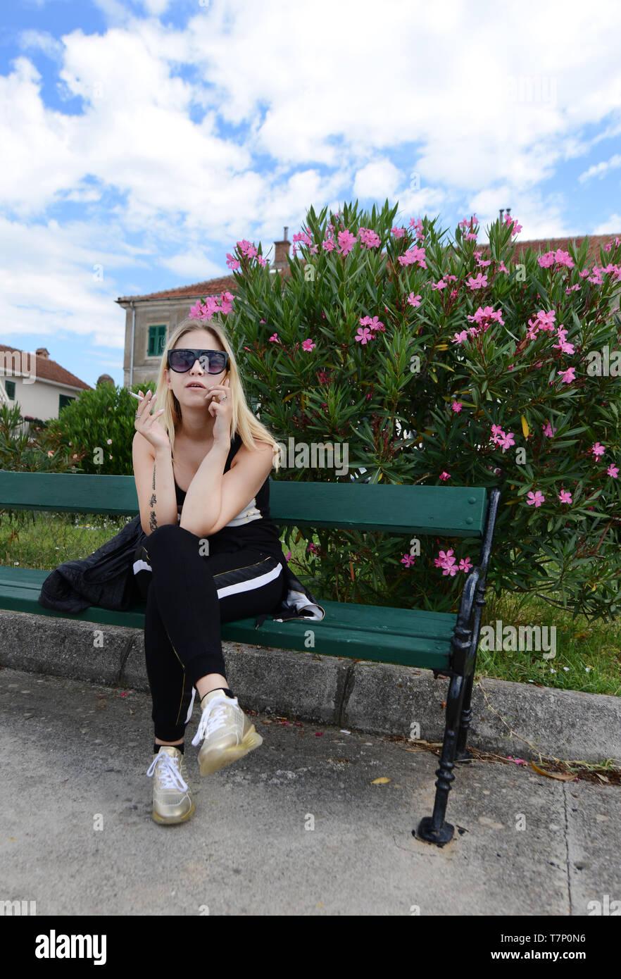 A fashionable Montenegrin woman smoking a cigarette. Stock Photo