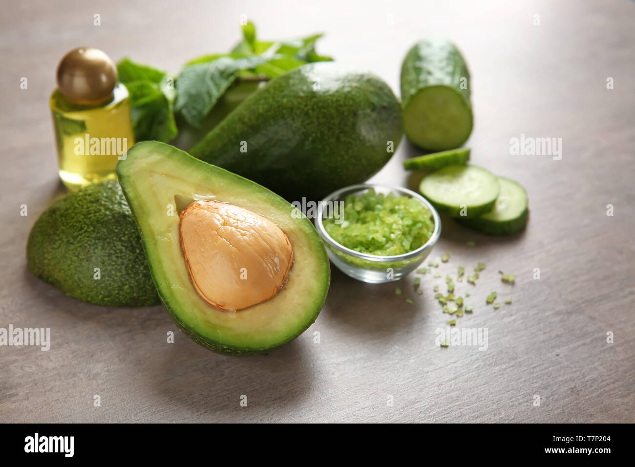 Avocado with ingredients for natural homemade cosmetics on grey