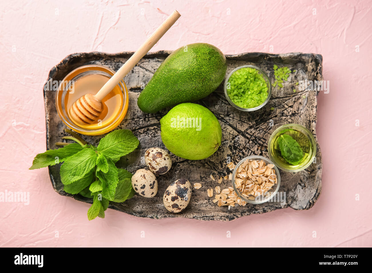 Plate with avocado and ingredients for natural homemade cosmetics on