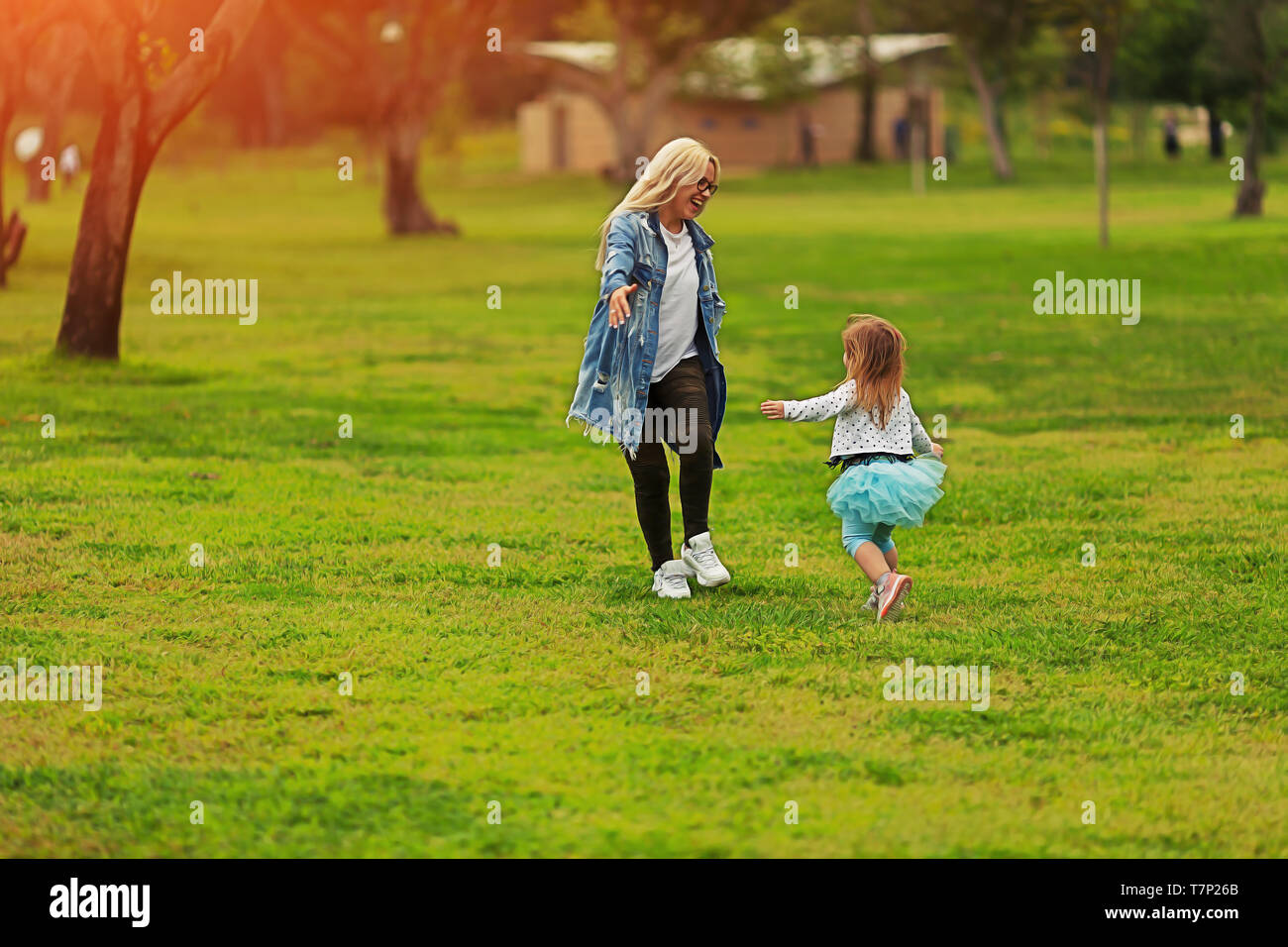 Toddler girl running to her mother in the park - Stock Image