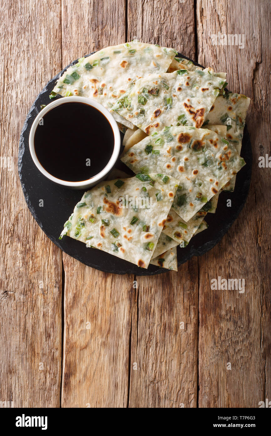 Vegan Scallion Pancakes are a crispy pan-fried Chinese flatbread close-up on a board on the table. Vertical top view from above - Stock Image