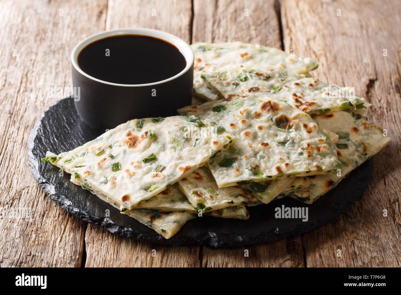 simple recipe for Chinese fried onion pancakes served with sauce close-up on a board. Horizontal - Stock Image