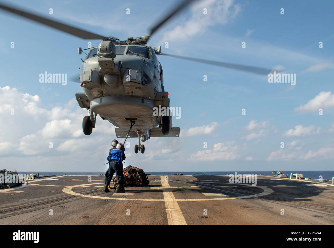 """190507-N-UI104-0380 SOUTH CHINA SEA (May 7, 2019) Sailors hook up palets to a MH-60R Seahawk assigned to the """"Easyriders"""" of Helicopter Maritime Strike Squadron (HSM) 37, Detachment ONE, aboard the Arleigh Burke-class guided-missile destroyer USS Preble (DDG 88) during a replenishment-at-sea.  Preble is deployed to the U.S 7th Fleet area of operations in support of security and stability in the Indo-Pacific region. (U.S. Navy Photo by Mass Communication Specialist 1st Class Bryan Niegel/Released) - Stock Image"""