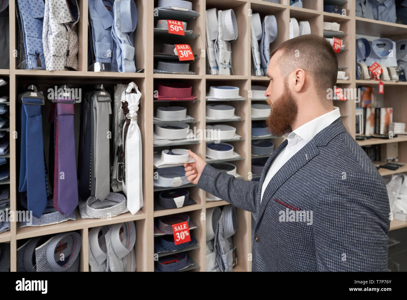 a9a17f7fe02 View from back of bearded male client standing near racks with clothes and  choosing new shirt