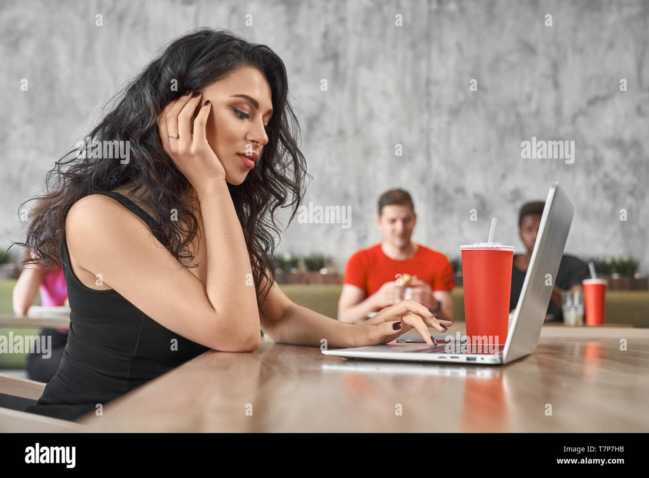 Serious female freelancer sitting in cafe and working with computer. Pretty brunette doing online job and surfing in internet while having lunch in pizzeria. Concept of network and job and wifi. Stock Photo
