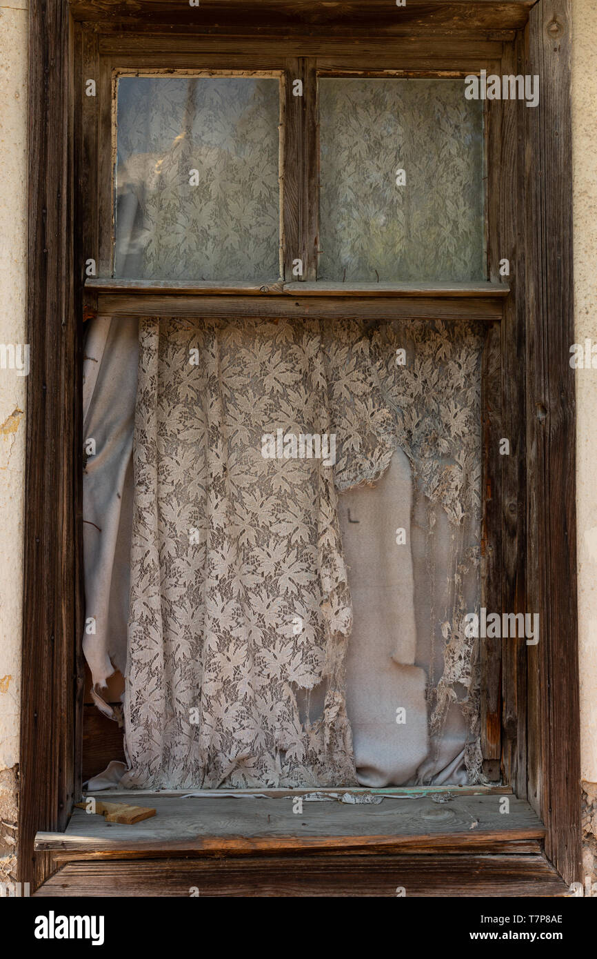 tattered curtain at a glassless window in an abandoned house - Stock Image