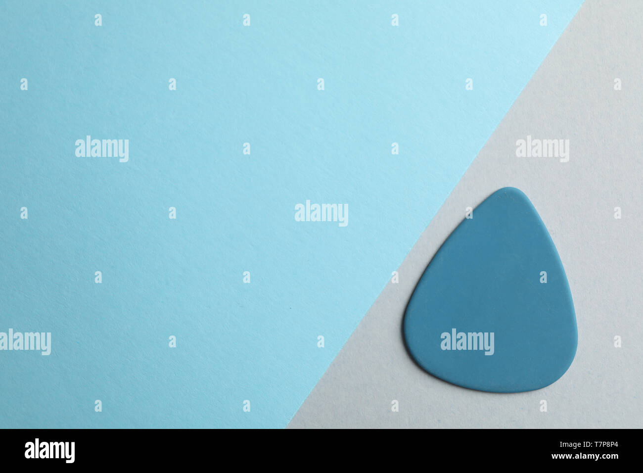 Blue guitar pick on two tone background, space for text - Stock Image