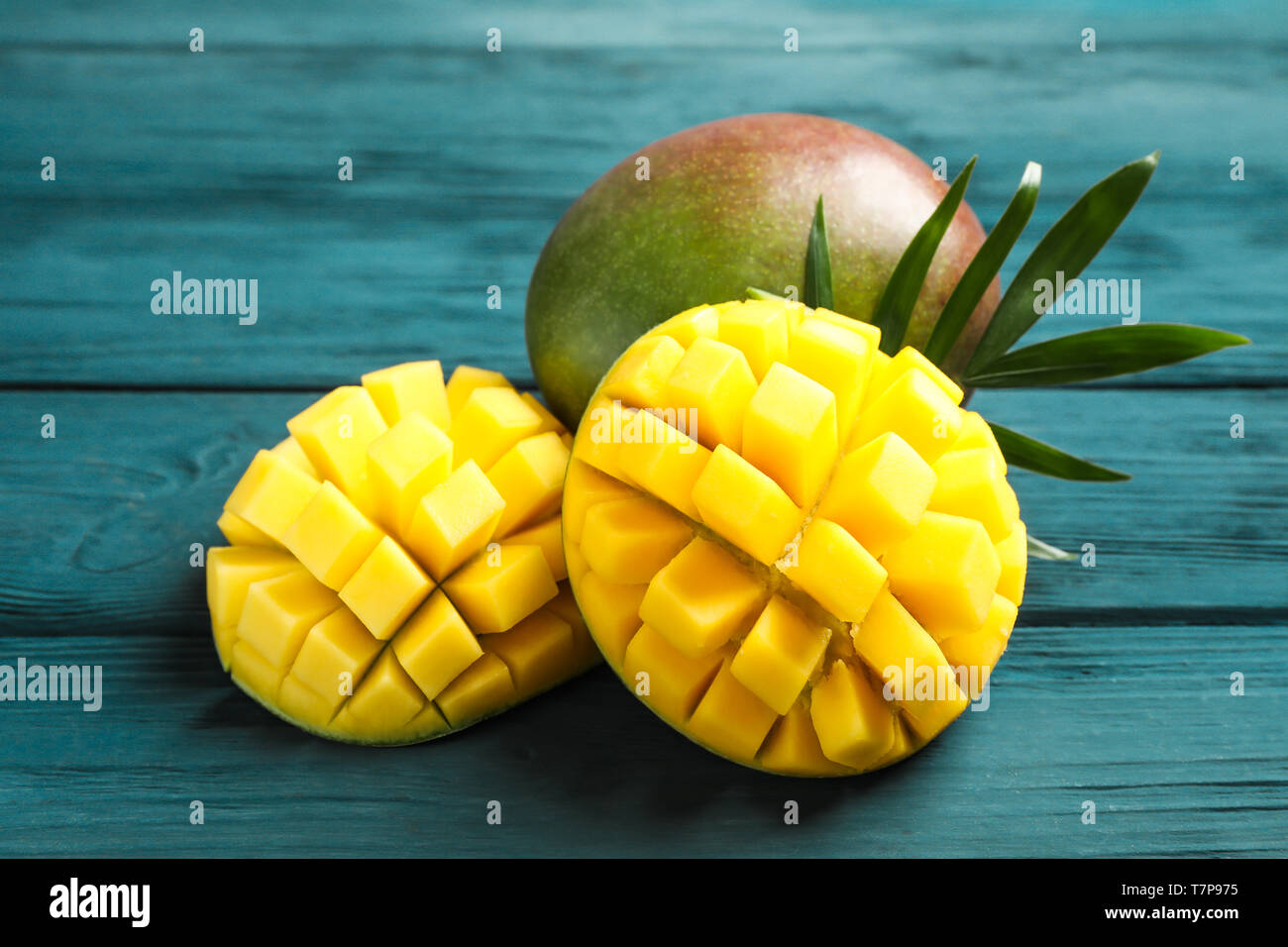 Cut ripe mangoes and palm leaf on wooden background, closeup Stock Photo