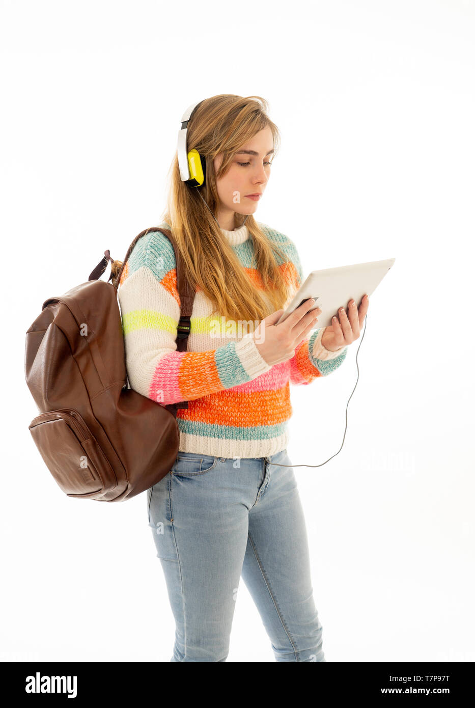 Portrait of happy young teenager student woman in headphones using tablet watching a video tutorial online curse or listening to music. Isolated white - Stock Image