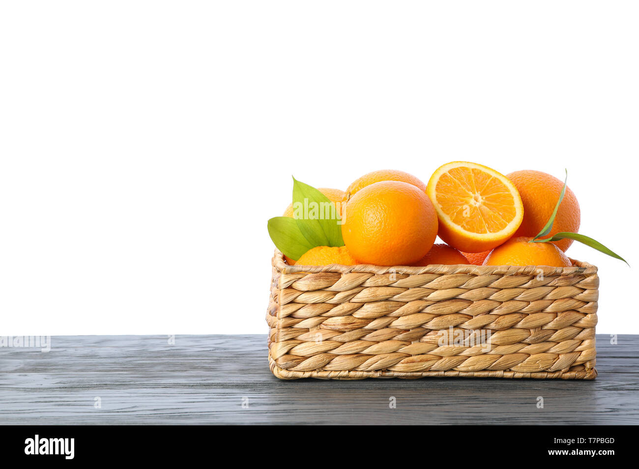 Wicker basket with ripe oranges on wooden table isolated on white background. Citrus food - Stock Image