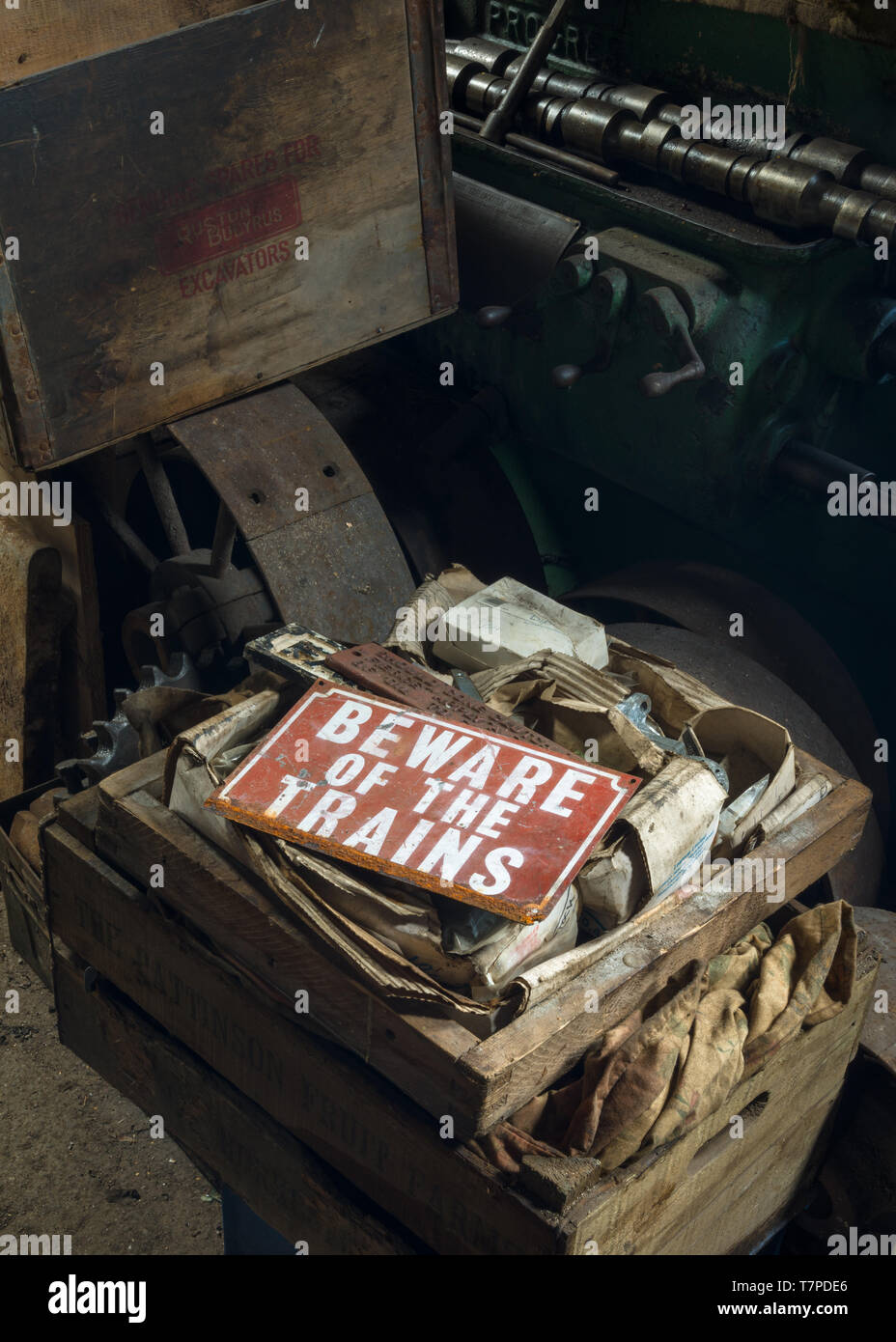 A vintage, red 'Beware of the Trains' sign lying unused in a train engineers workshop, the Mining Museum, Lake District, UK - Stock Image