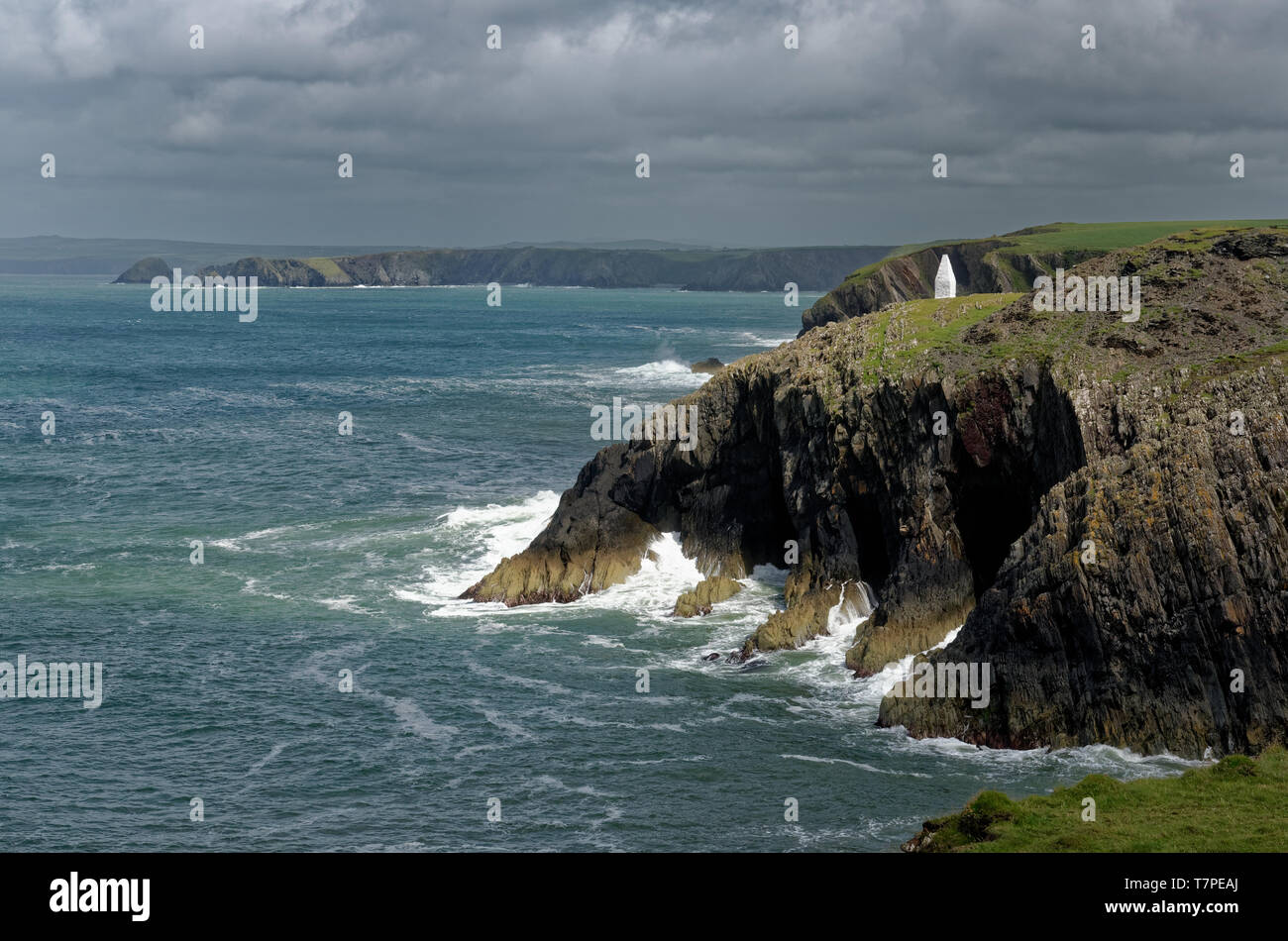 Dramatic cliffs and a white stone navigation marker in the sunlight on the Pembrokeshire Coast Path at the entrance to Porthgain harbour, Wales - Stock Image