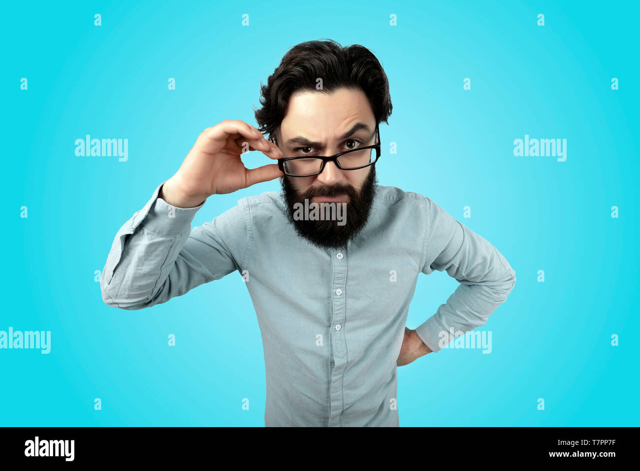 Headshot of strict annoyed aggressive man with beard, mustache, looks seriously through spectacles, frowns face in dissatisfaction, expresses negative - Stock Image