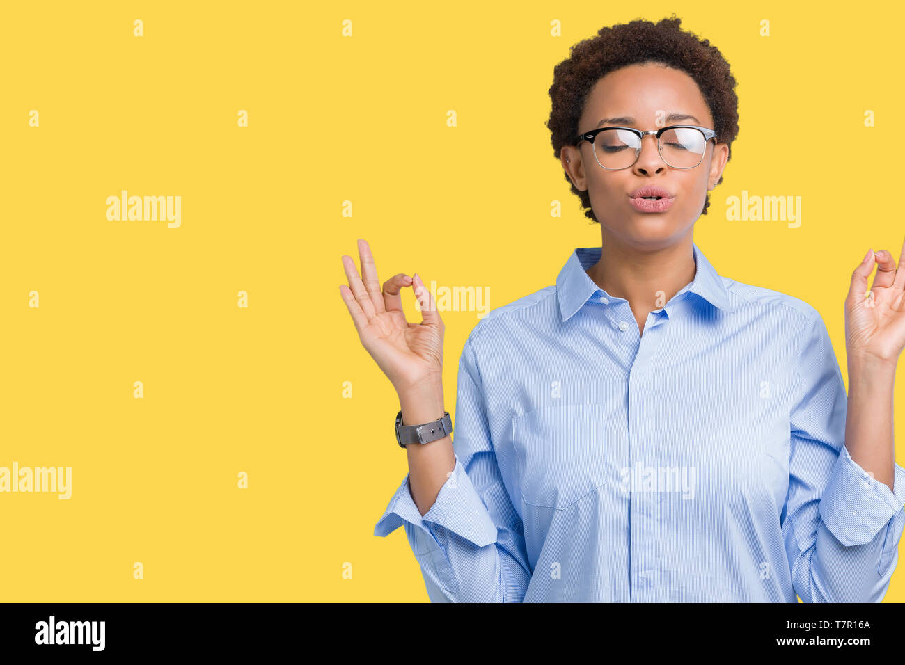 Young beautiful african american business woman over isolated background relax and smiling with eyes closed doing meditation gesture with fingers. Yog - Stock Image