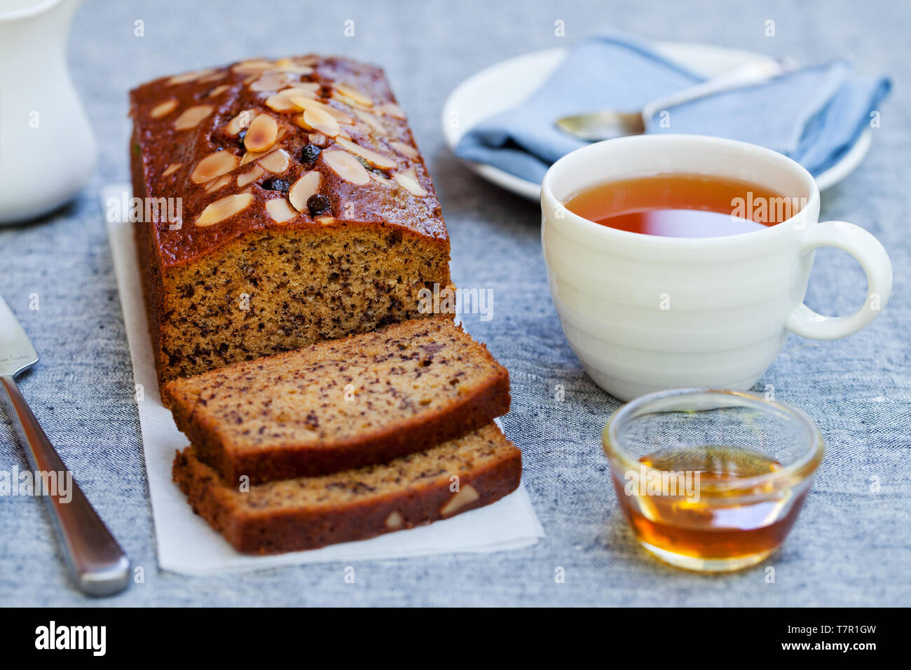 Banana, carrot, apple cake, loaf with chocolate and cup of tea on grey background. Stock Photo