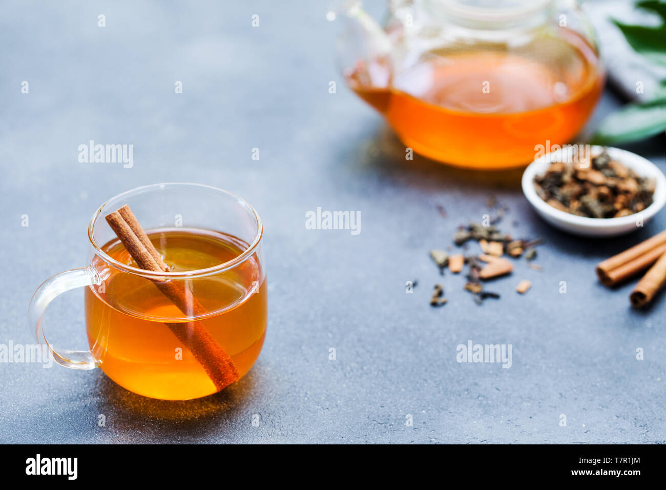 Tea with cinnamon in glass cup and teapot on grey stone background. Copy space. Stock Photo