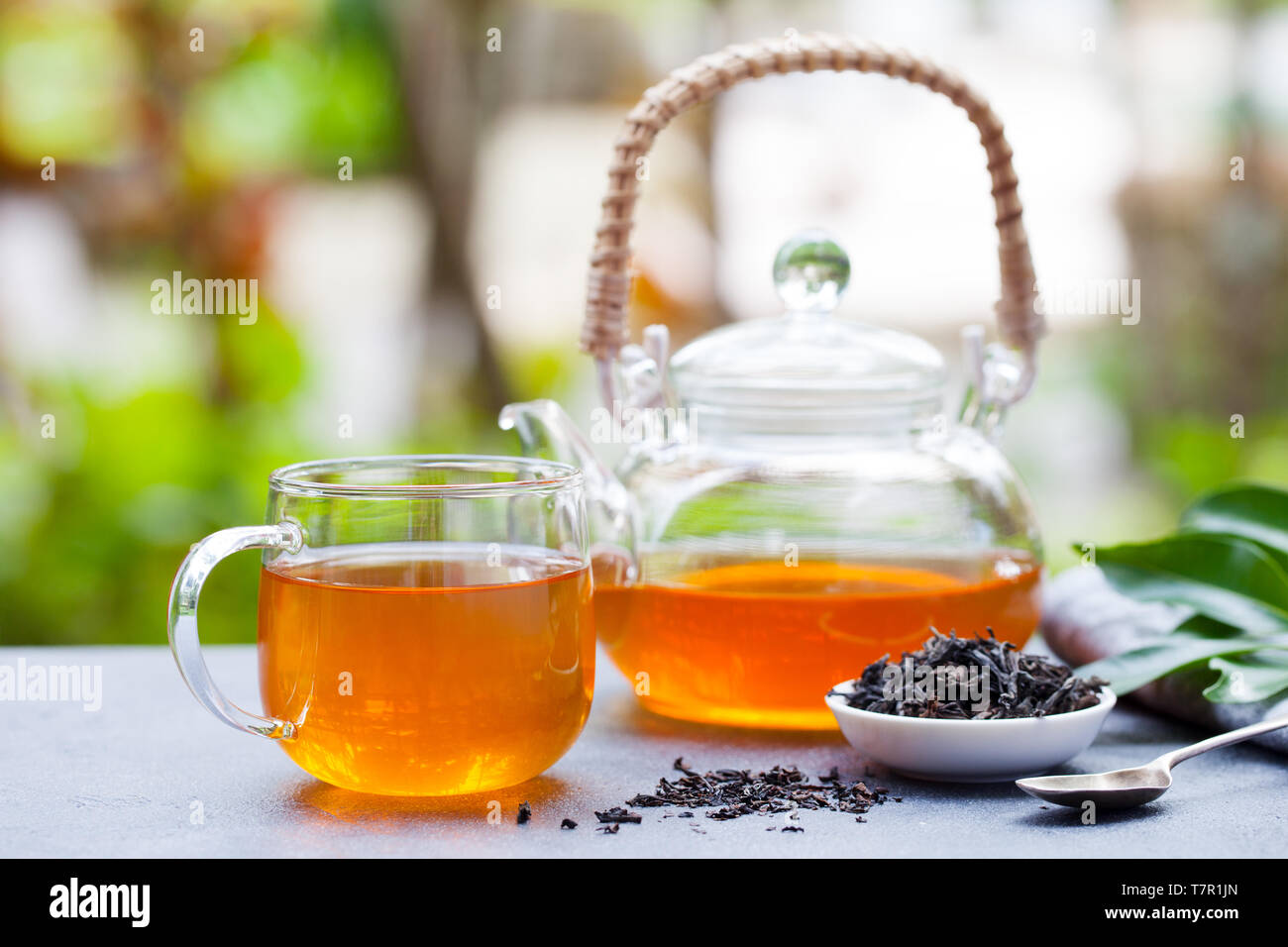 Black tea in glass cup and teapot on summer outdoor background. Copy space. Stock Photo