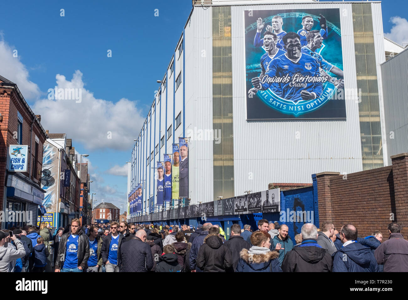 Everton, Liverpool, UK, April, 17, 2016: Crowds supporters gather at Everton Football Club for a premiership game versus Southampton, flags and scarfs  in the Everton colours can be seen, against a bright blue sky Stock Photo