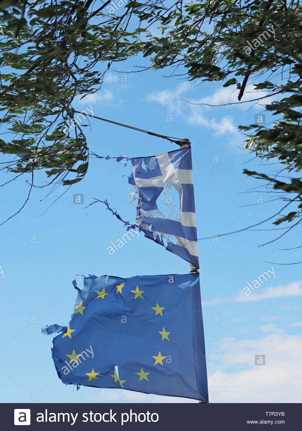 damaged by the wind, isolated flags of European union and Greece, illustrating the results on any single country after years of cooperation within the - Stock Image
