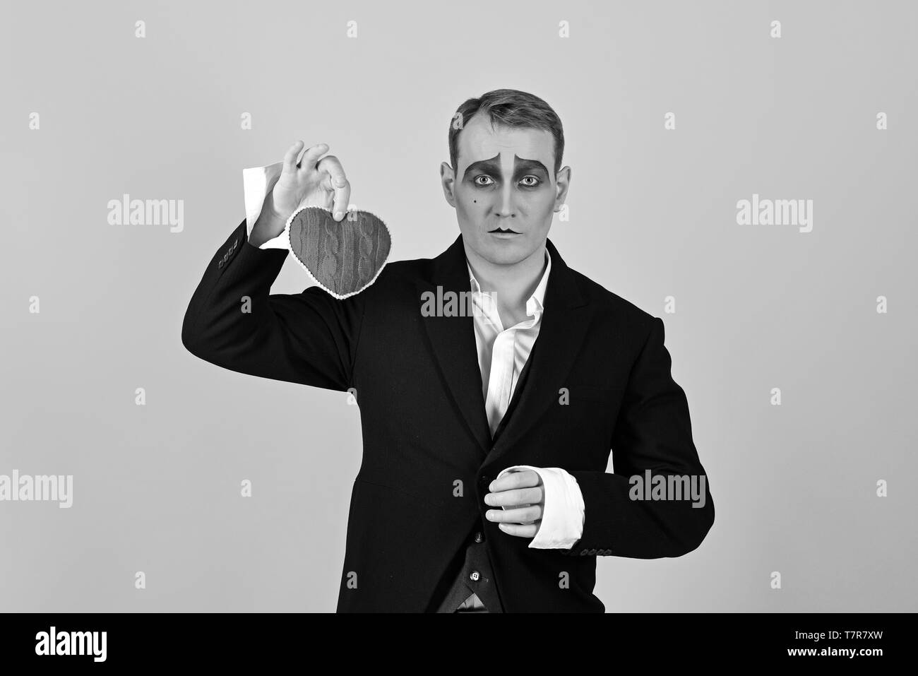 I love melancholy. Mime actor with love symbol. Mime man hold red heart for valentines day. Theatre actor pantomime falling in love. Love confession - Stock Image