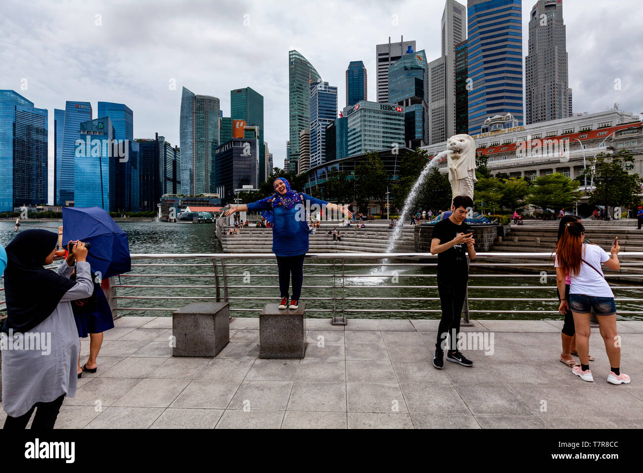 Tourists Posing For Photos In Front Of The Merlion Statue and Singapore Skyline, Singapore, South East Asia Stock Photo