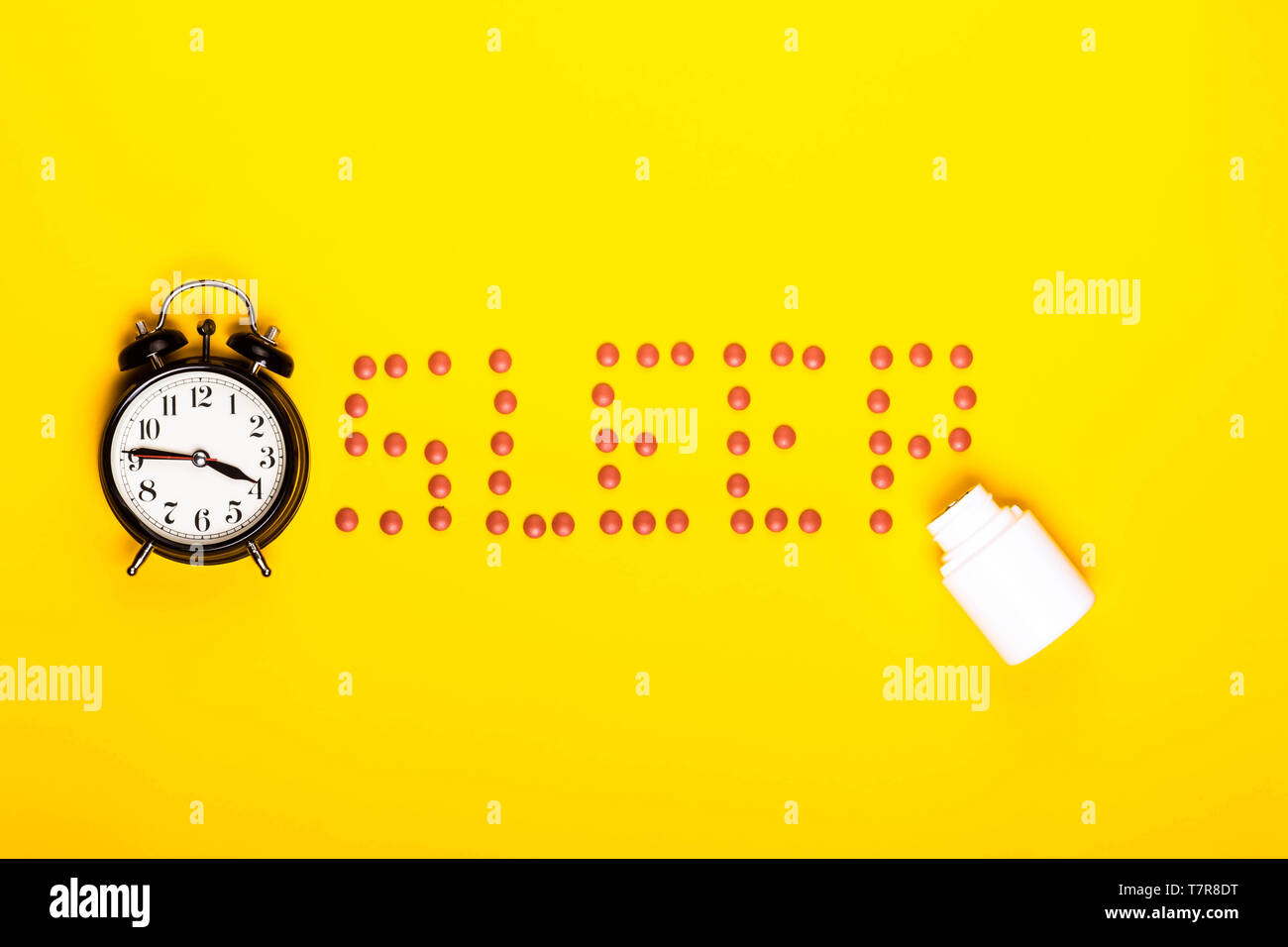 Sleep concept showing sleeping pills and an alarm clock on a yellow background - Stock Image