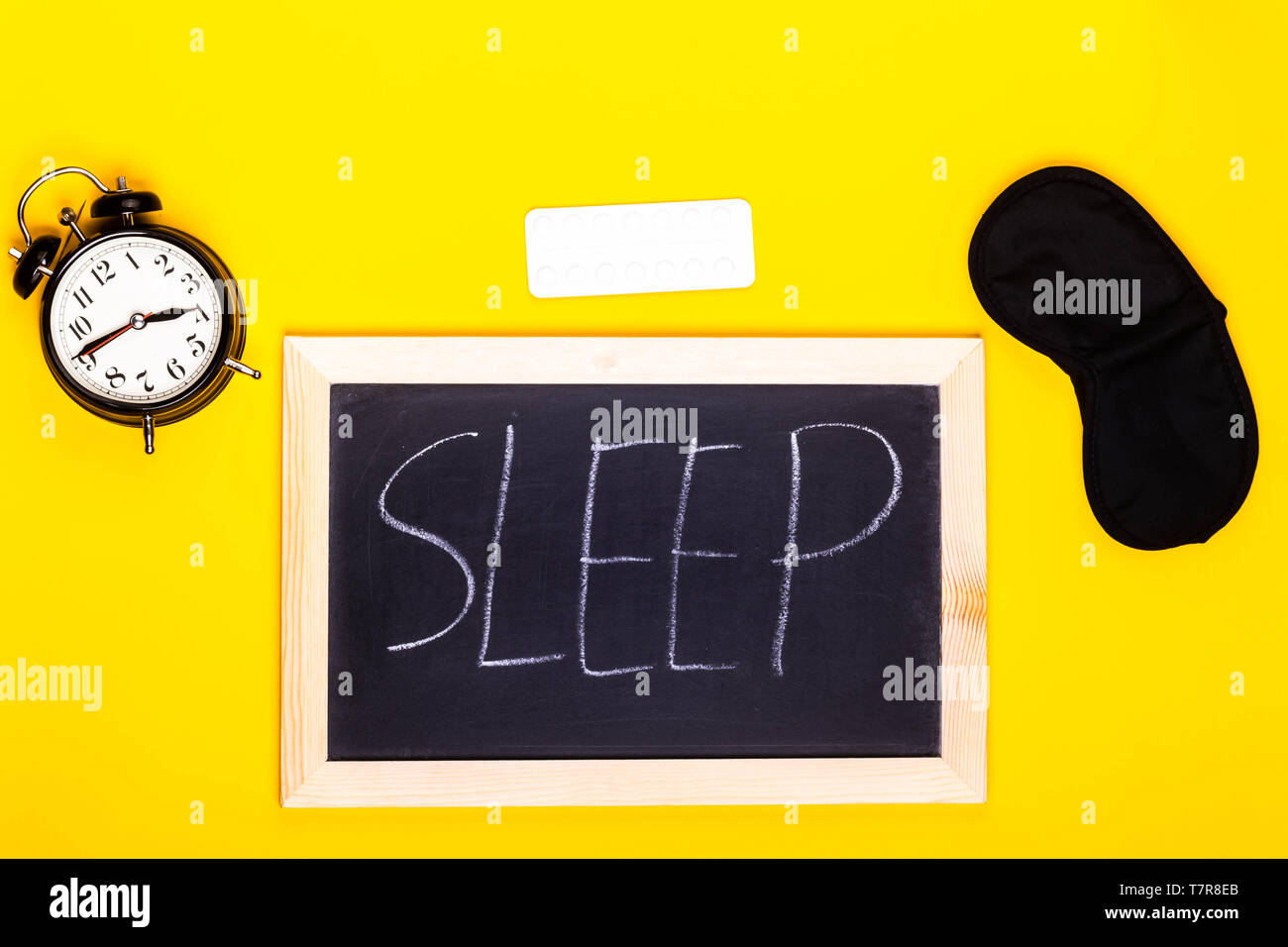 Sleep concept showing a blackboard spelling sleep with an alarm clock, sleeping pills and an eye mask - Stock Image
