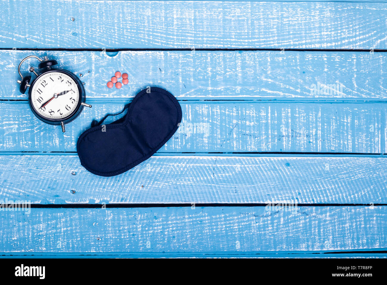 Sleep concept showing an alarm clock, sleeping pills and eye mask on a weathered blue background - Stock Image