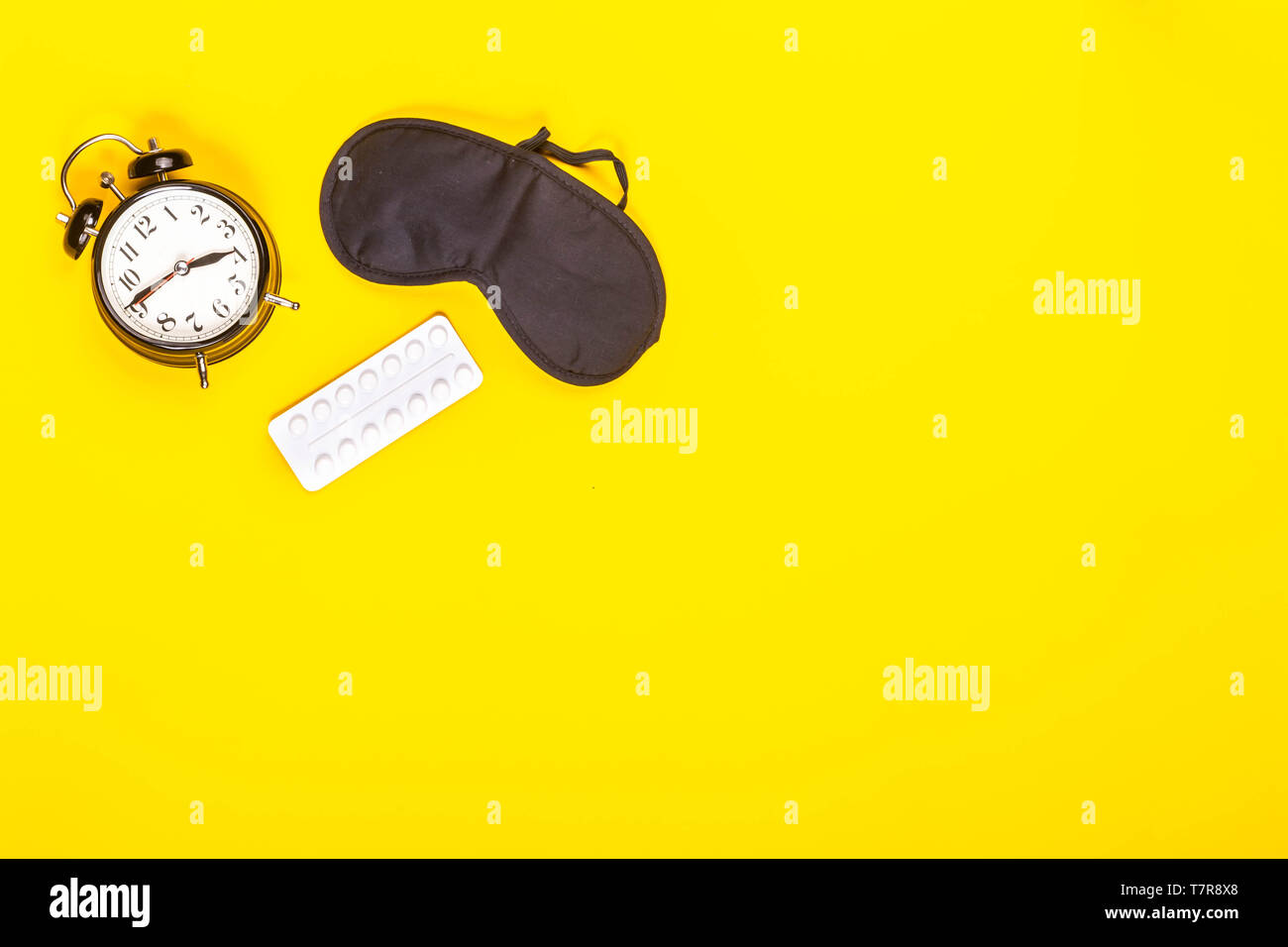 Sleep concept showing an eye mask, alarm clock and sleeping pills on a yellow background - Stock Image