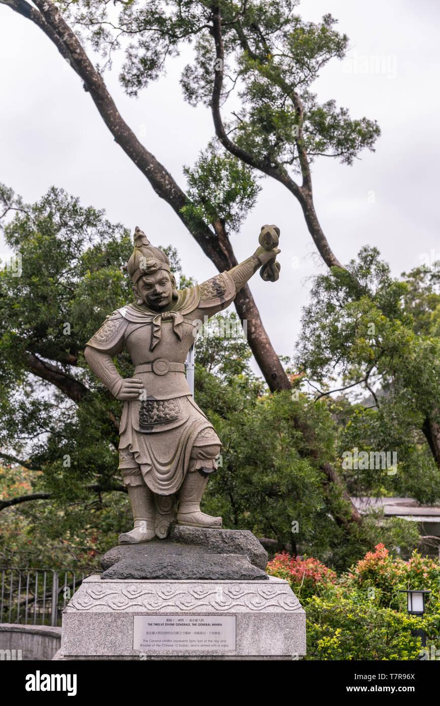 Hong Kong, China - March 7, 2019: Lantau Island. Po Lin Buddhist Monastery. Stone statue of General Mihira, one of the twelve Divine Generals. Green B - Stock Image